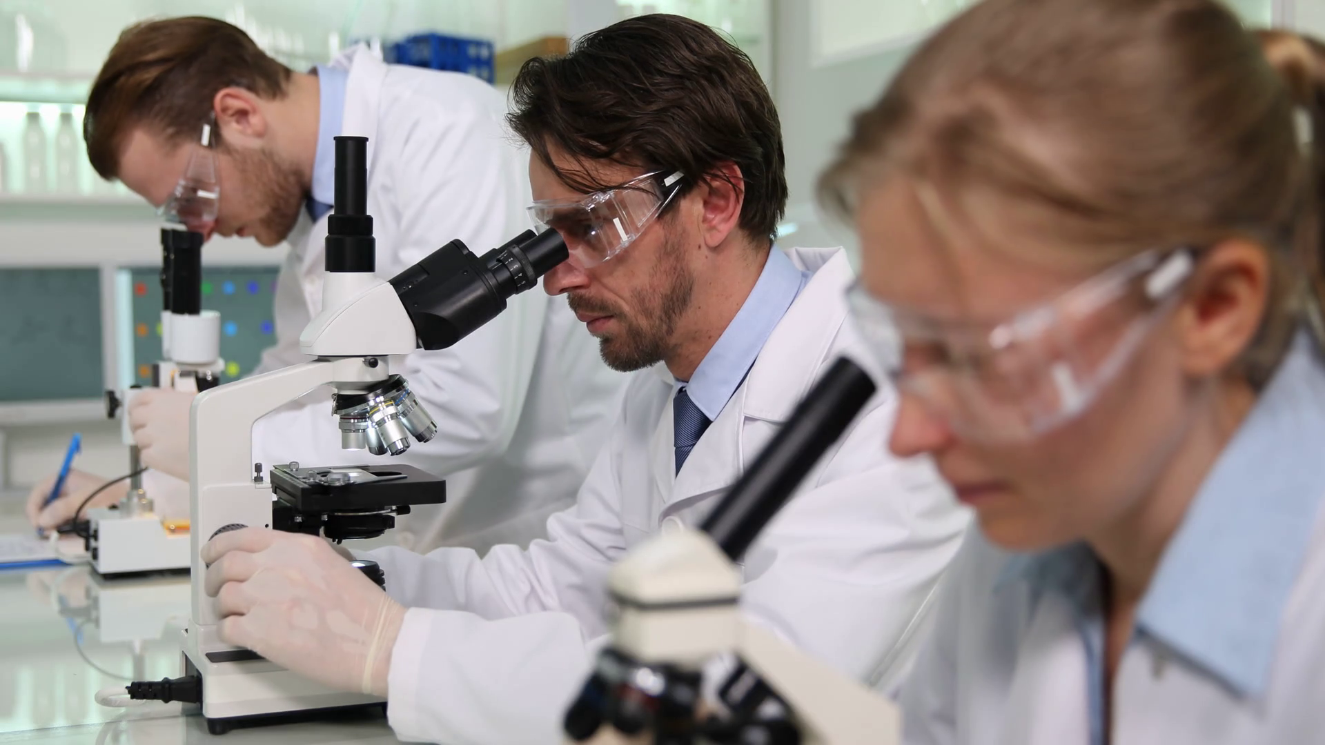 videoblocks-hospital-microbiology-laboratory-team-of-researchers-work-activity-on-microscope_r_x3-kkx2x_thumbnail-full01