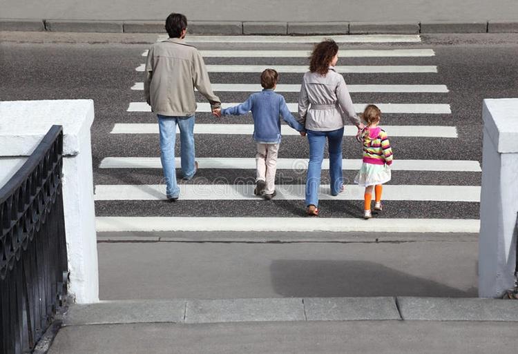 i-genitori-tiene-la-mano-dei-bambini-e-della-strada-dell-incrocio-20570697_